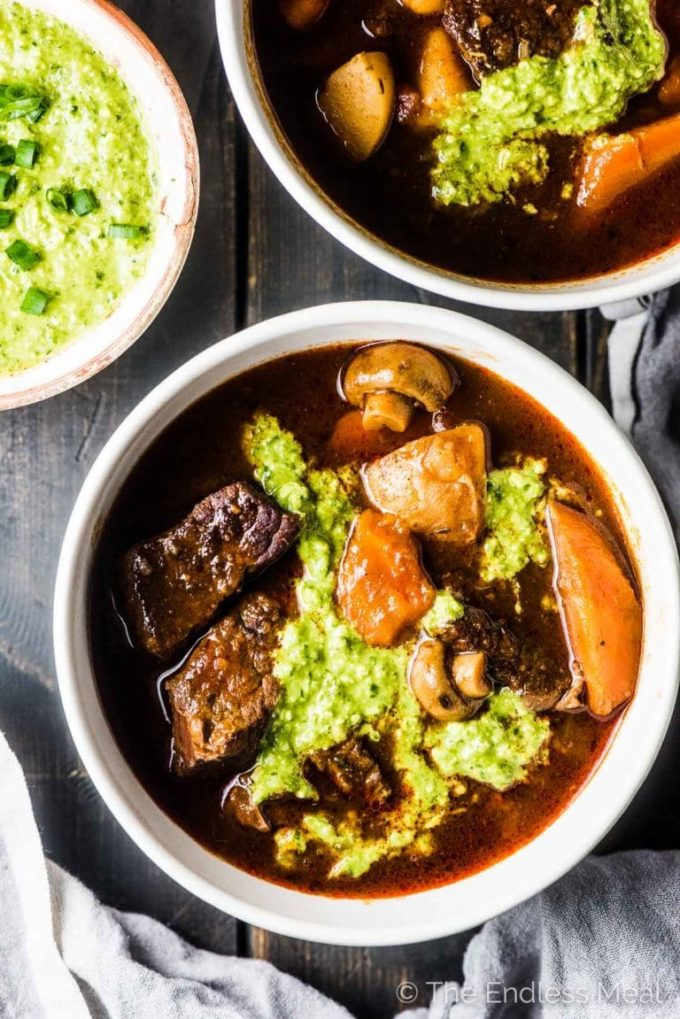 Two white bowls full of beef stew, topped with green sauce