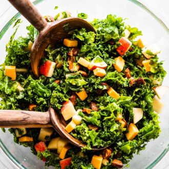 Kale apple salad in a bowl with wooden salad tongs.