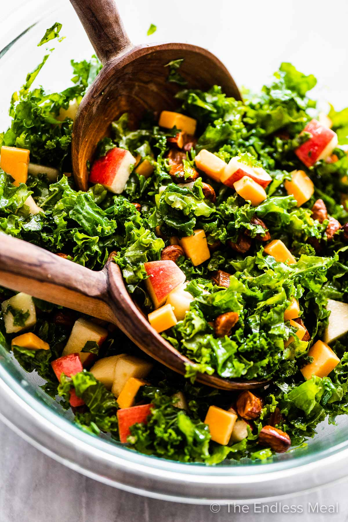 A close up of kale apple salad in a glass bowl with wooden salad tongs.