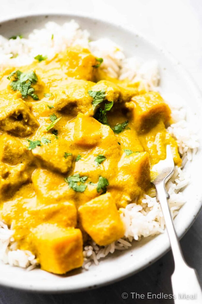 Mango chicken curry in a bowl with rice and a fork.