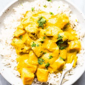 A white bowl with mango chicken curry on rice and a fork in it.