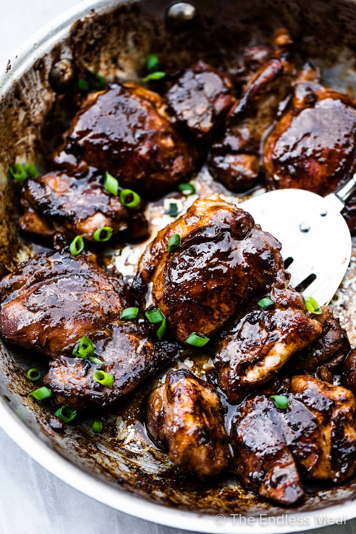 Soy sauce chicken in a pan with a spatula lifting a piece.