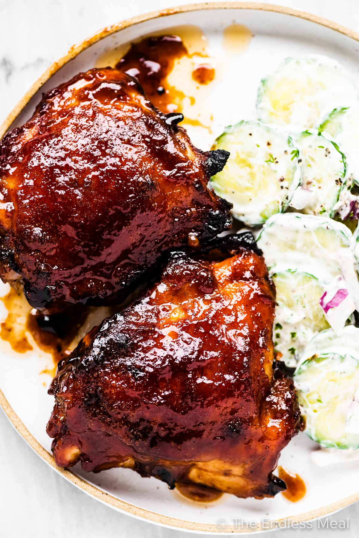 Two pieces of baked bbq chicken on a white plate with a side of cucumber salad.