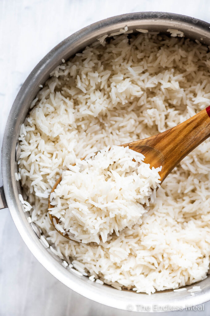 stovetop basmati rice in a pot with a wooden spoon.