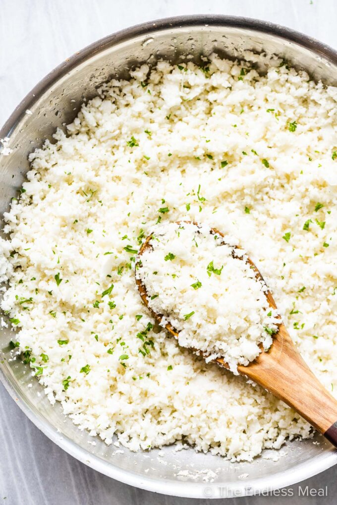 cauliflower rice in a pan with a wooden spoon.