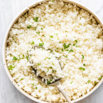 A white bowl with cauliflower rice and a spoon.