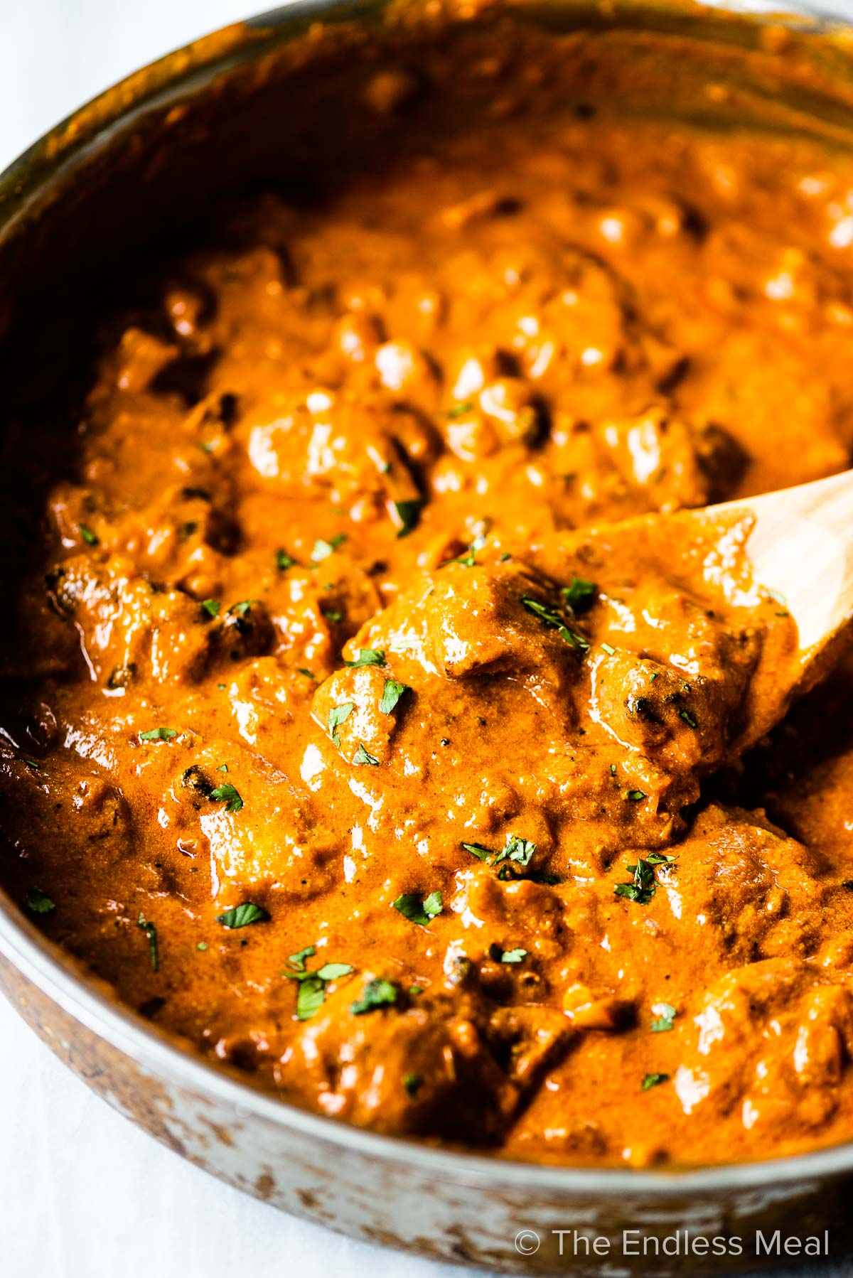 This chicken tikka masala recipe in a pan with a wooden spoon.