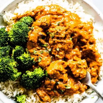 Chicken tikka masala on a plate with a side of rice and broccoli.