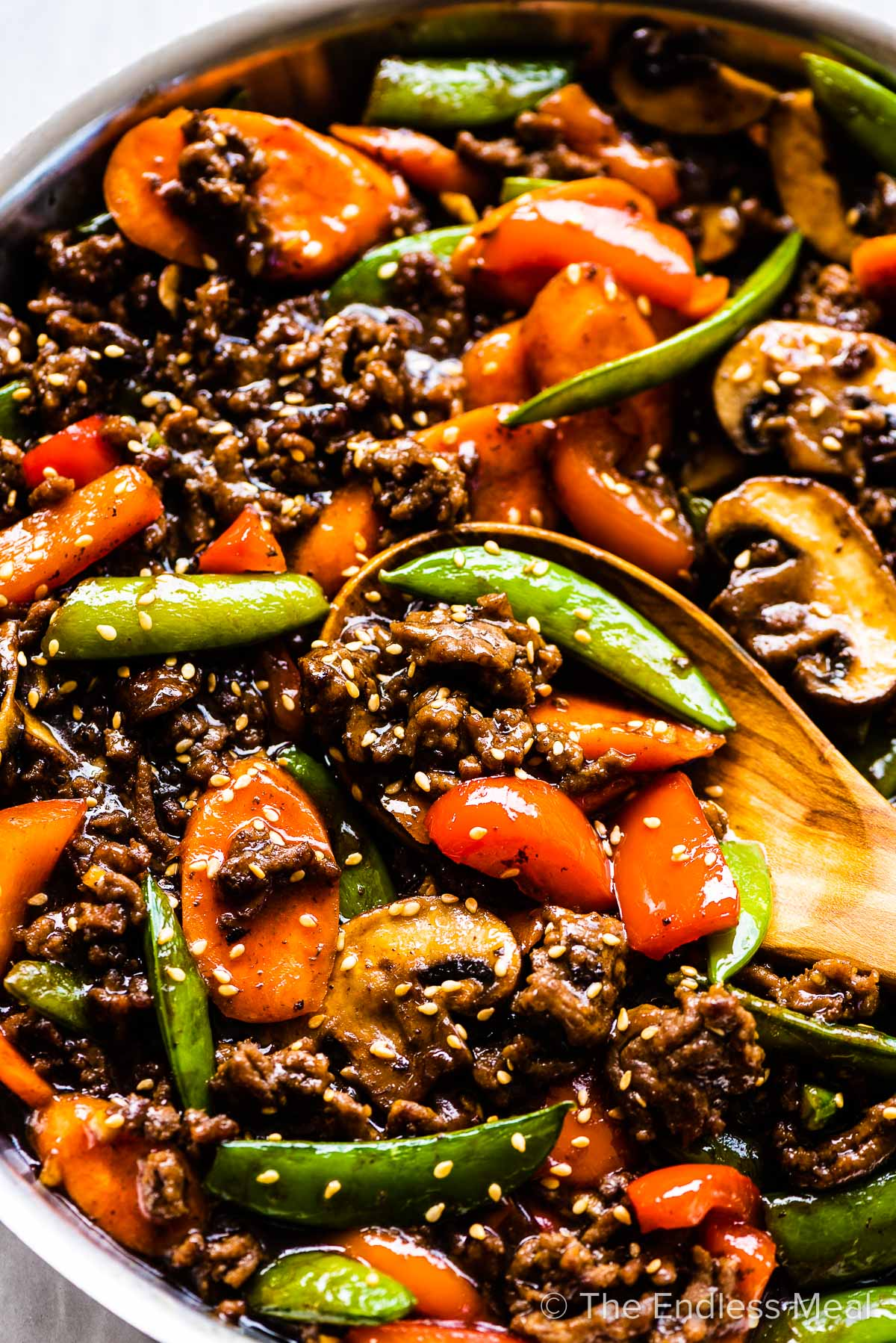 A close up of ground beef stir fry in a pan with lots of peppers, peas, carrots, and mushrooms.