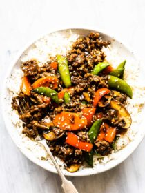 Ground beef stir fry on top of rice on a white plate.