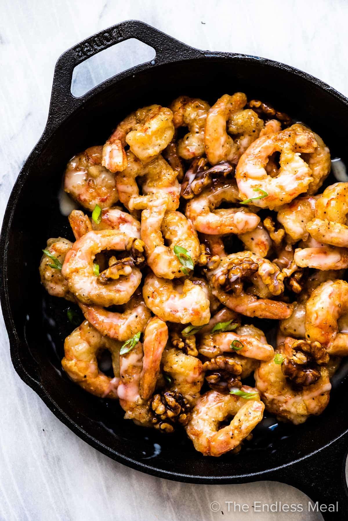 Honey walnut shrimp in a black pan.