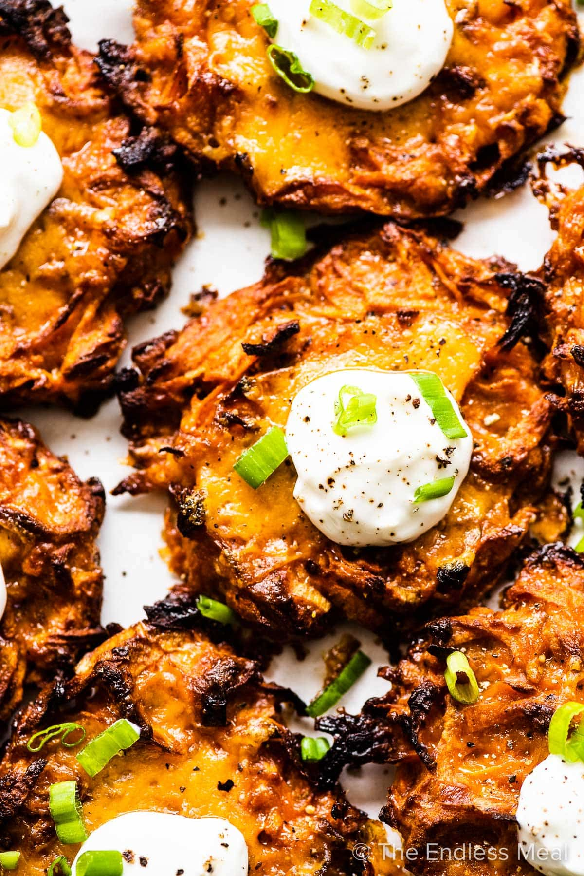 A close up of a sweet potato latke with sour cream on top.