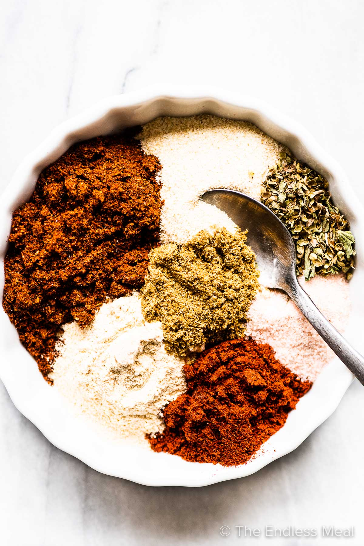 All the spices for this homemade fajita seasoning recipe in a bowl with a spoon.