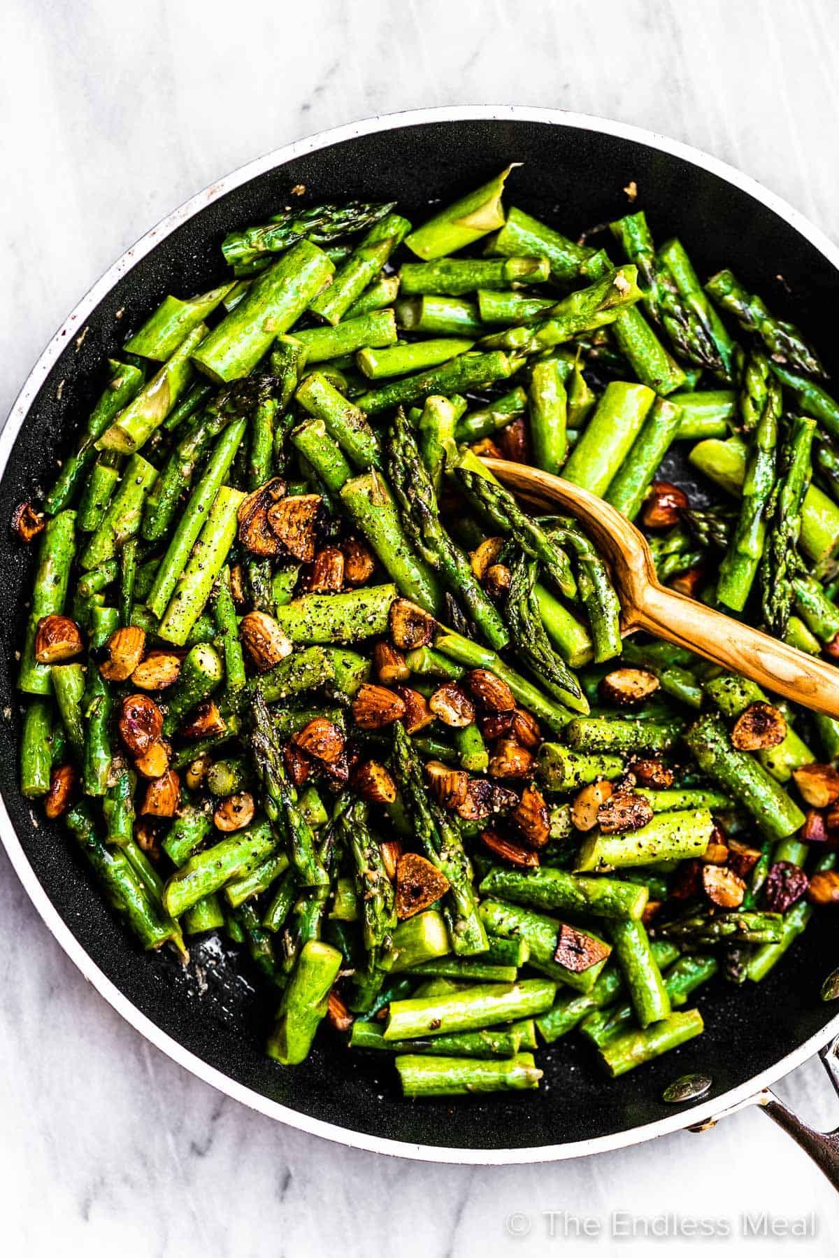 Garlic butter asparagus in a black pan.