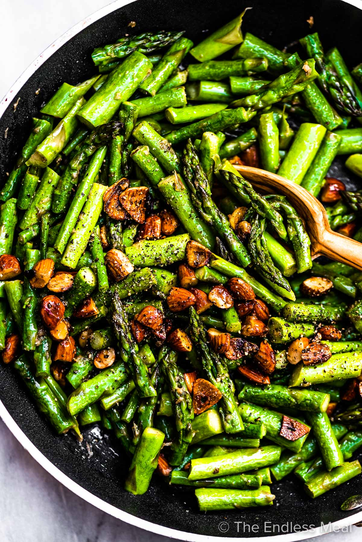 A pan of garlic butter asparagus with a wooden spoon taking a scoop.