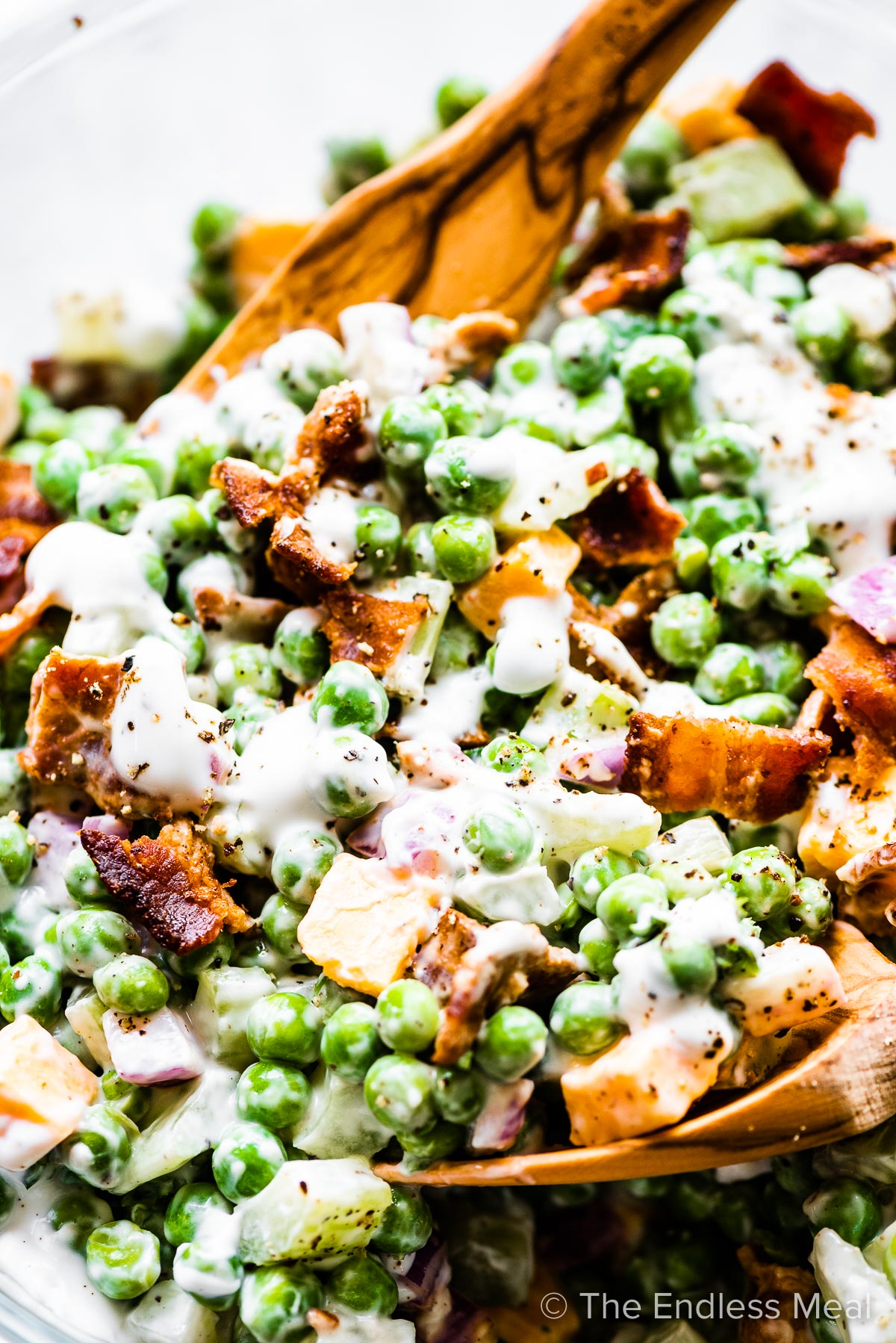 A close up of creamy pea salad with bacon.