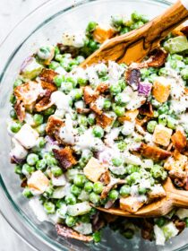 Creamy pea salad in a glass bowl with wooden salad tongs