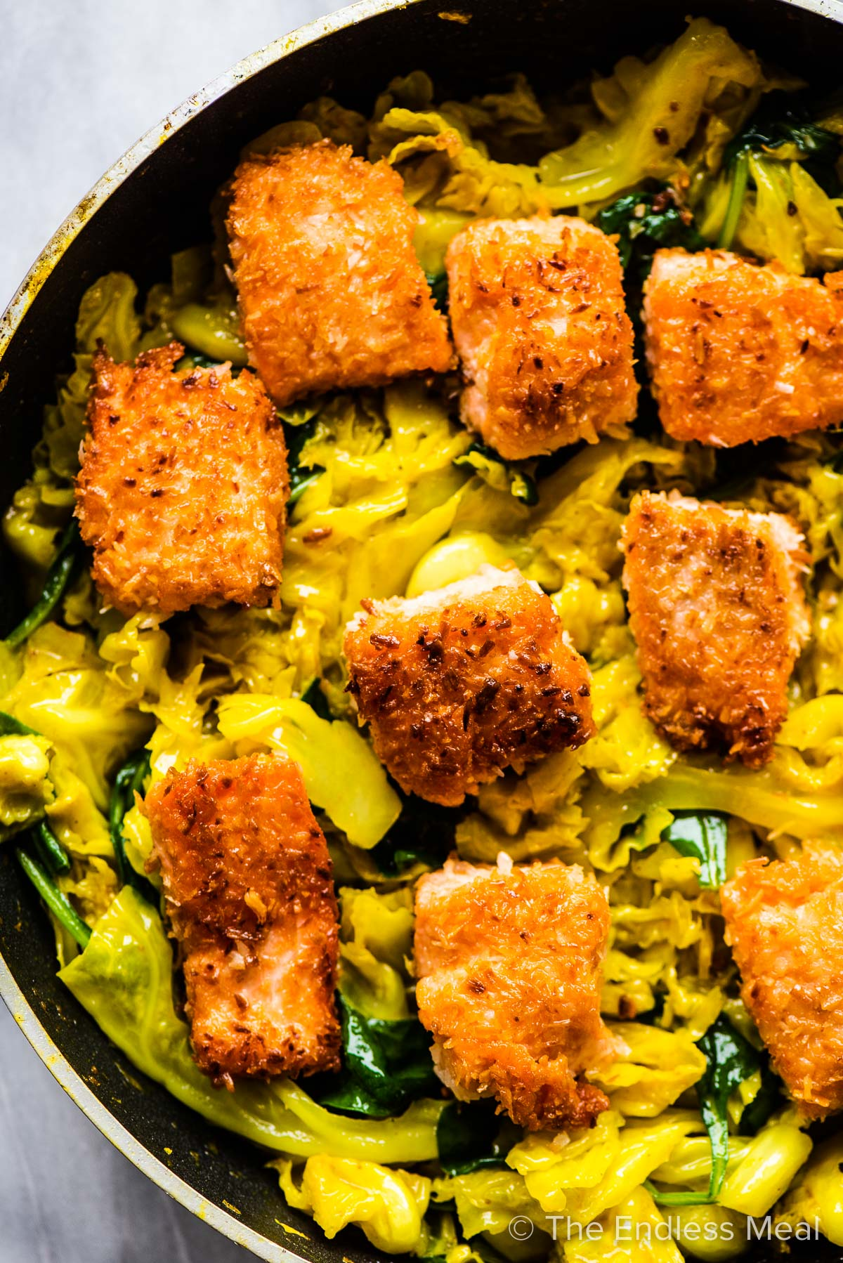 A pan with crispy salmon and cabbage.