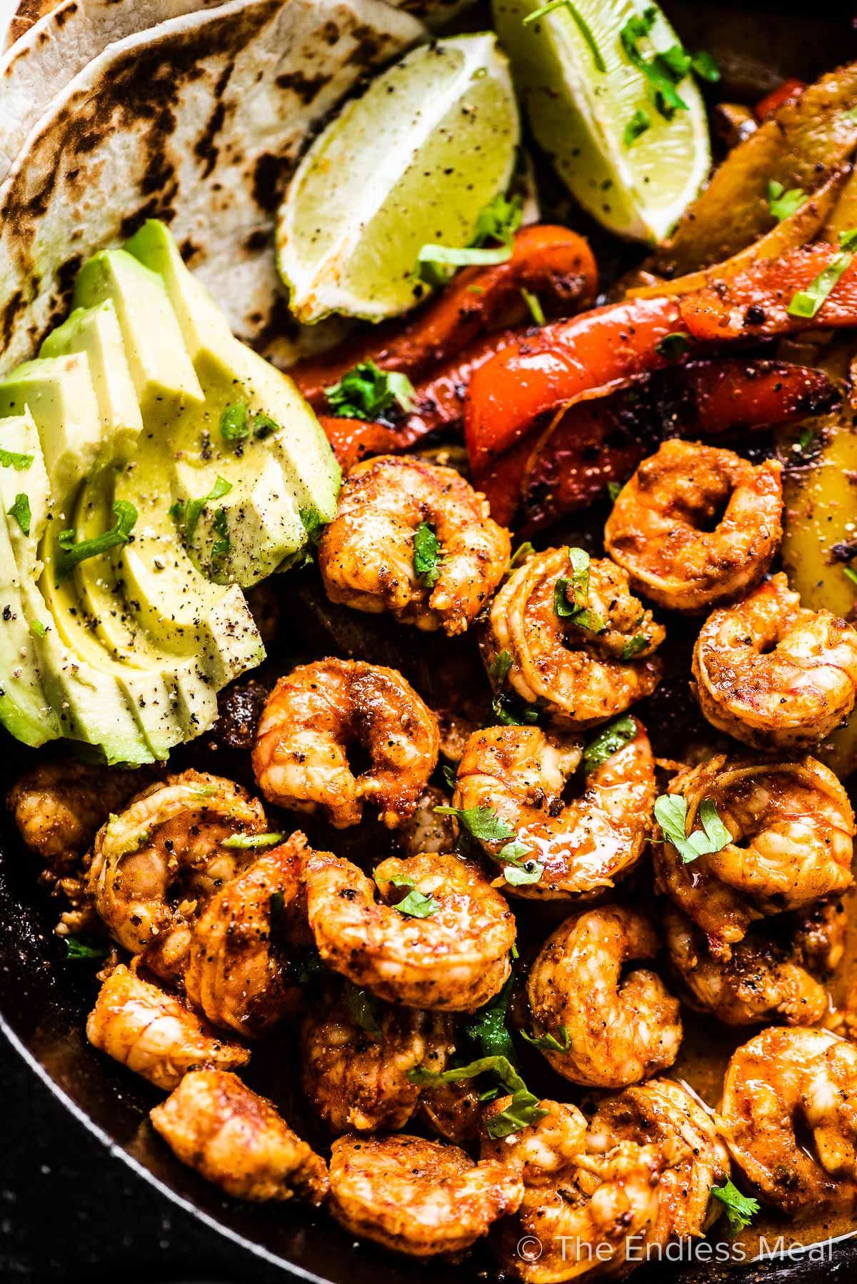 A close up of shrimp fajitas in a pan with avocado and limes.