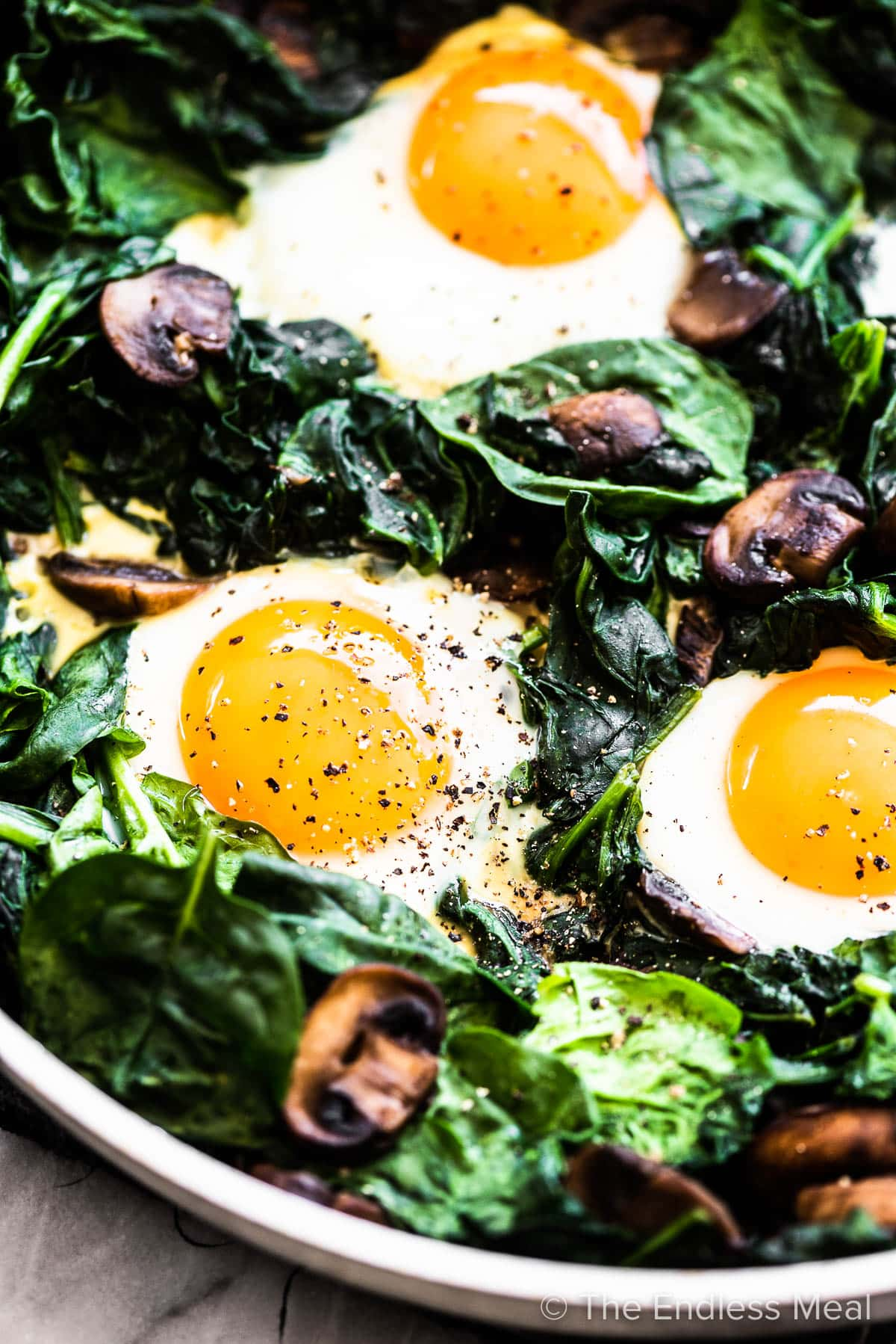 Fried eggs and spinach in a pan.