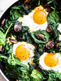Spinach and eggs in a pan.