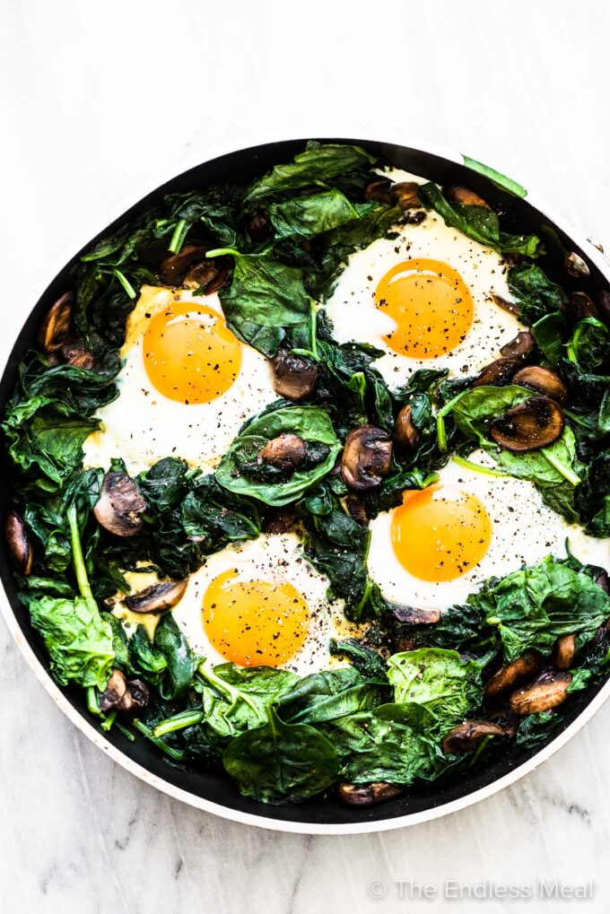 Spinach and eggs in a frying pan.