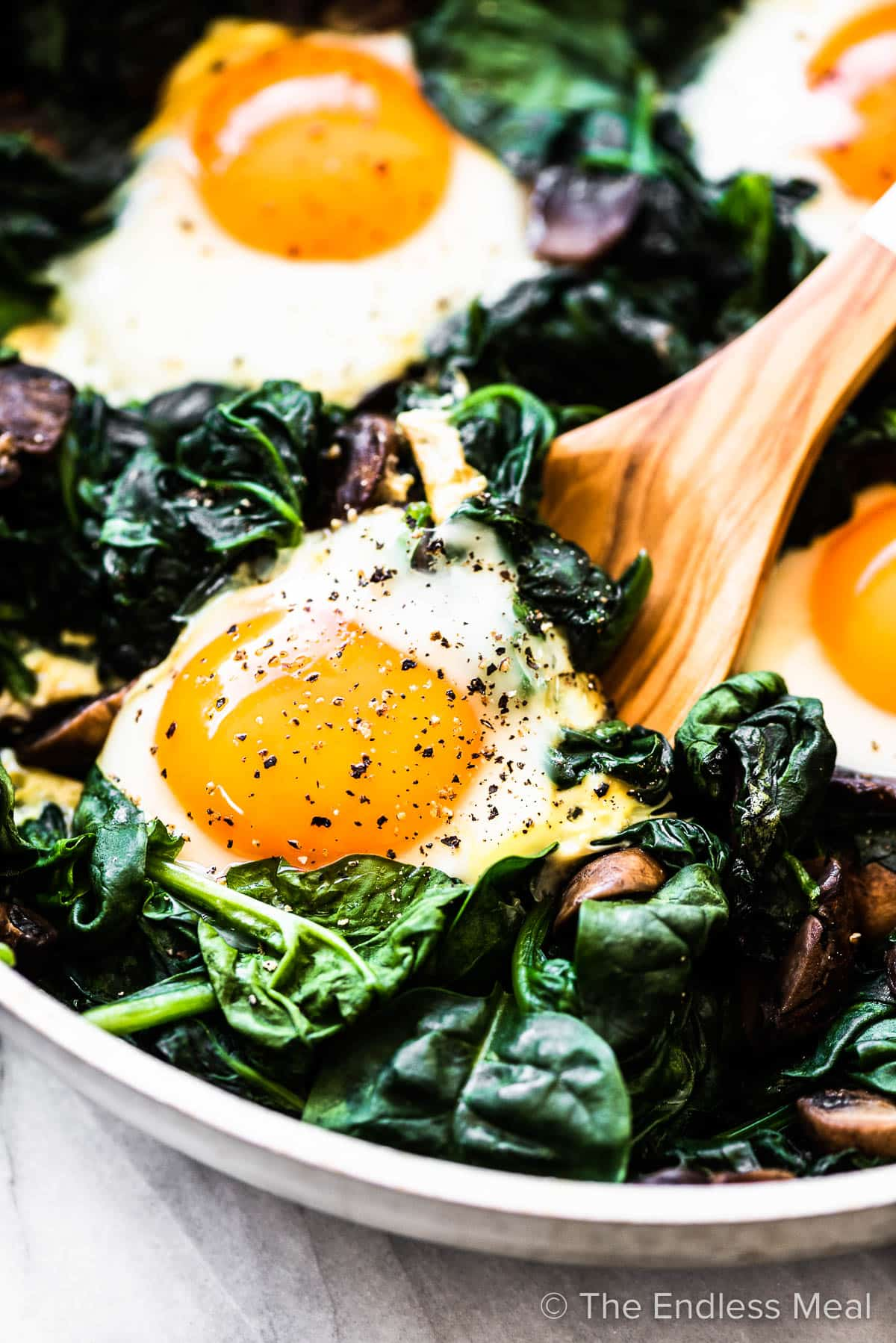 A closeup of a wooden spoon scooping some spinach and eggs out of a pan.