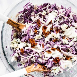 Blue Cheese Coleslaw in a glass bowl with bacon sprinkled on top.