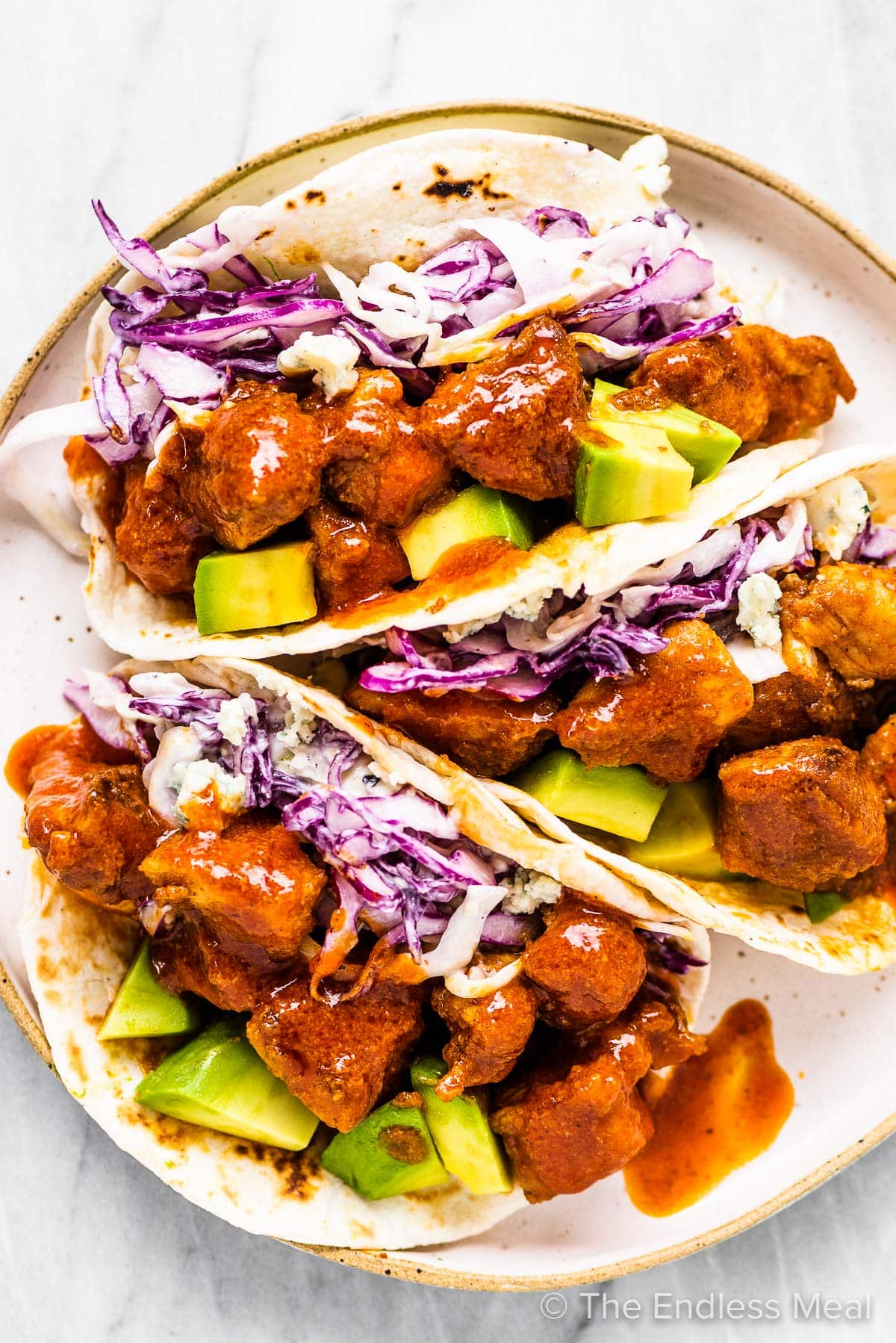 Three buffalo chicken tacos on a plate with coleslaw and avocados.
