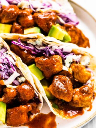 Buffalo chicken tacos on a white plate.