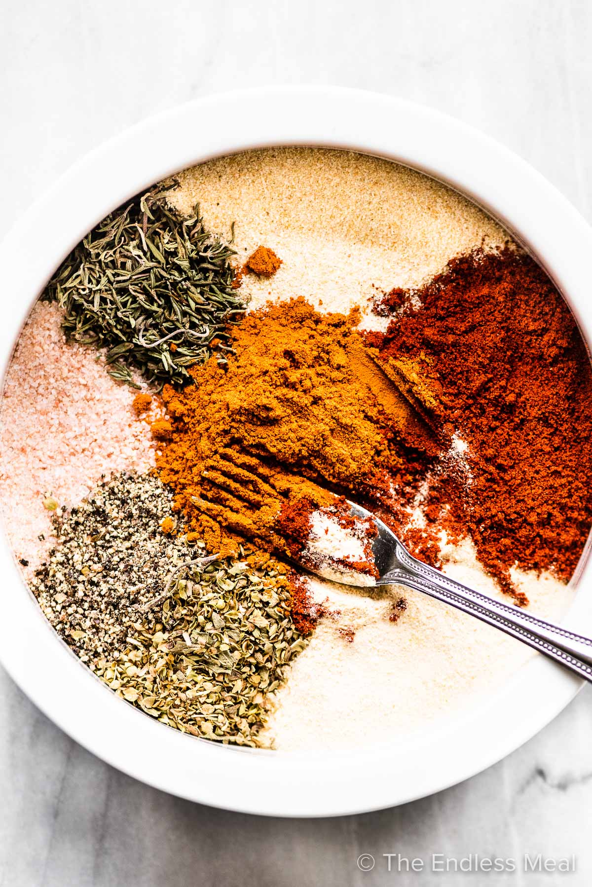 Cajun seasoning spices in a bowl with a fork.
