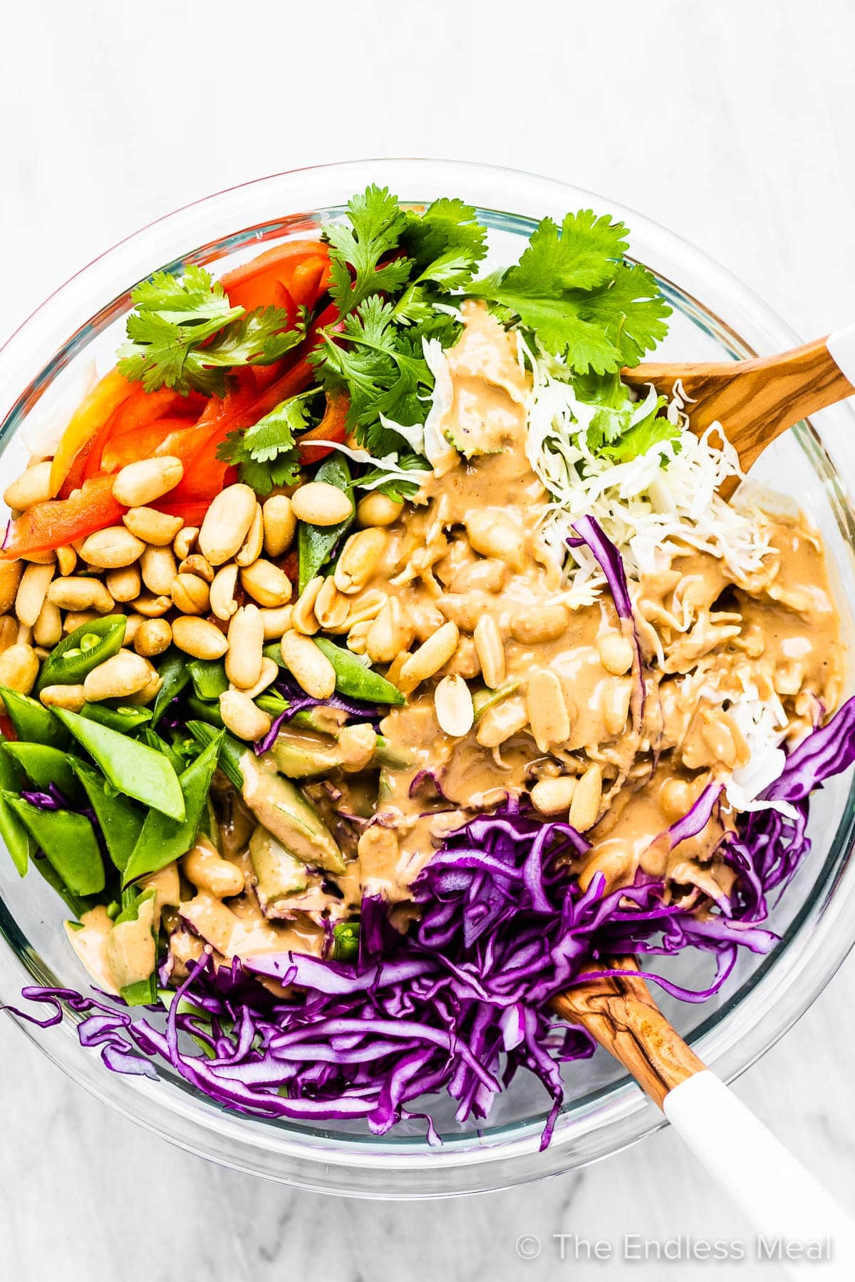 Peanut dressing poured over top of salad in a bowl.