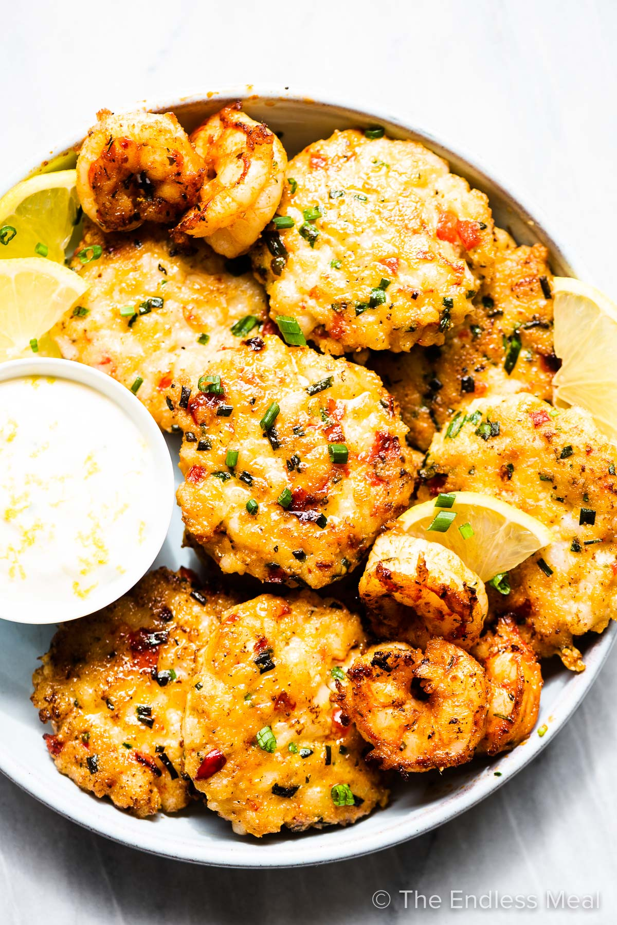 Tender shrimp cakes on a platter with a side of lemon aioli.