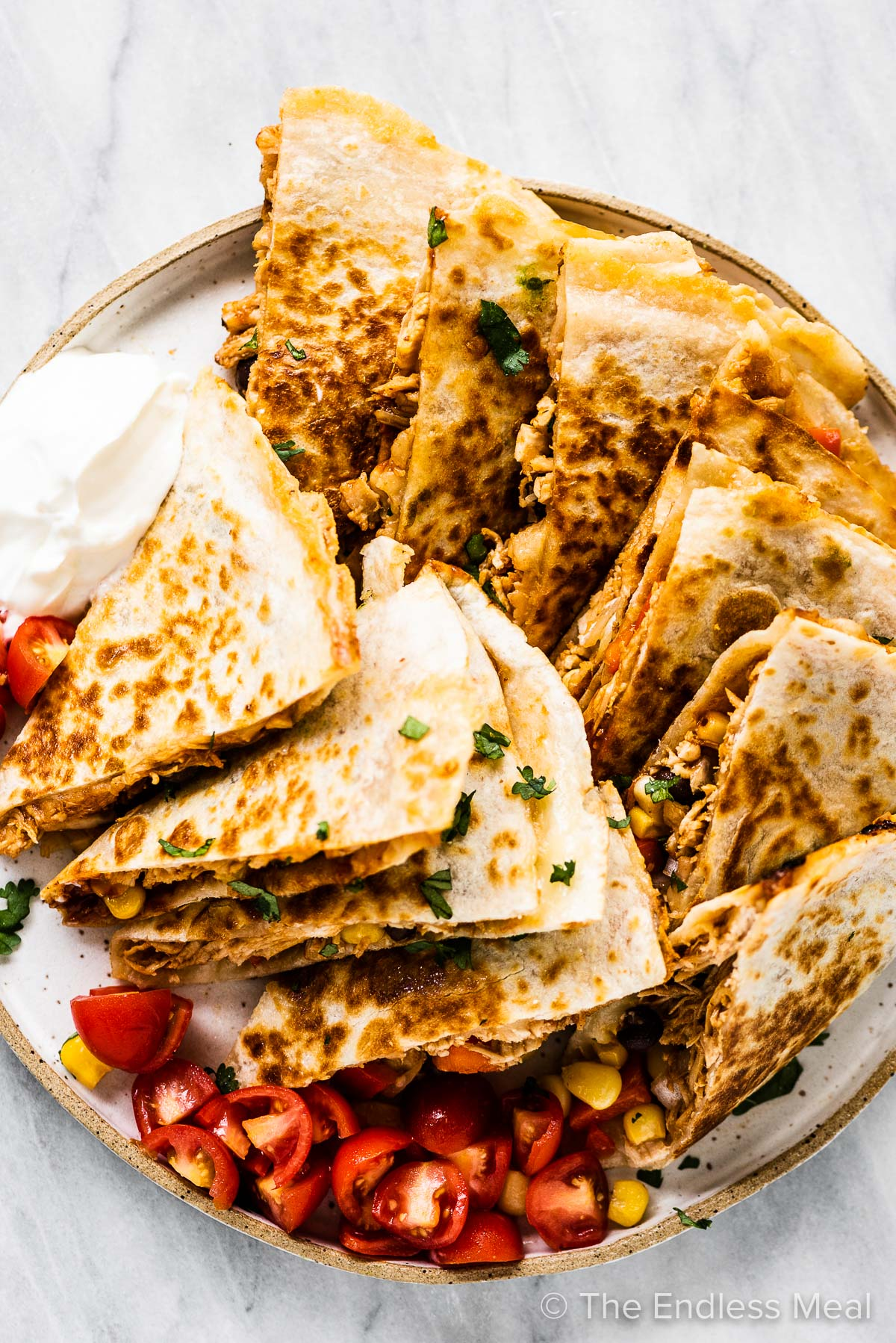 A plate piled high with bbq chicken quesadillas with salsa and sour cream on the side.