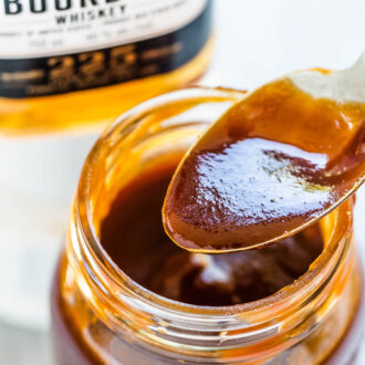 A jar of bourbon bbq sauce with a bottle of bourbon in the background.