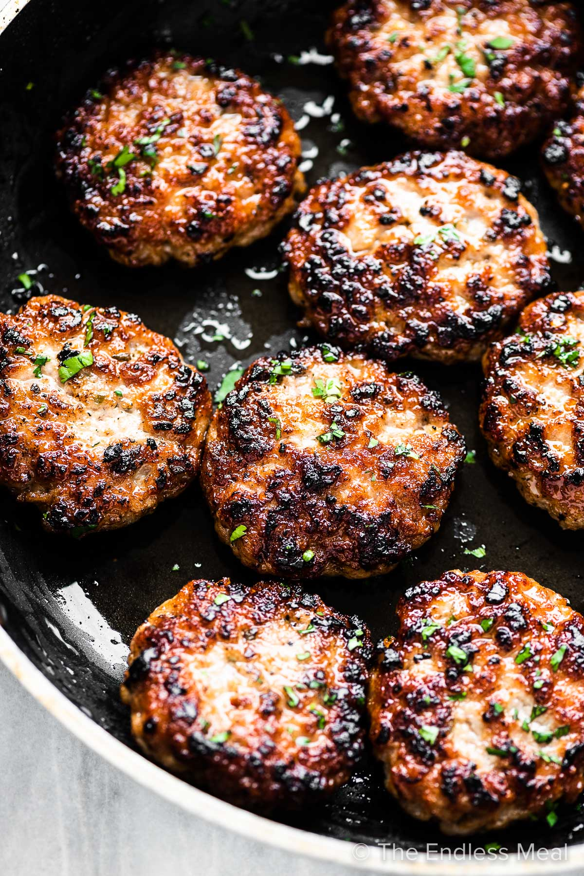 Homemade breakfast sausage patties in a pan.