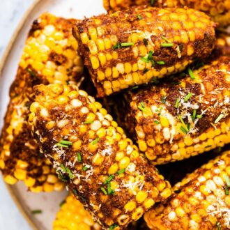 Cheesy corn on the cob piled high on a plate.
