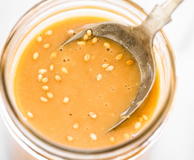 Sesame ginger dressing in a glass jar with a spoon in it.