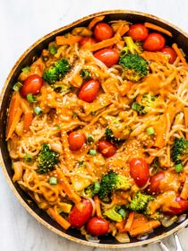 shirataki noodles in a pan with veggies and a peanut sauce.