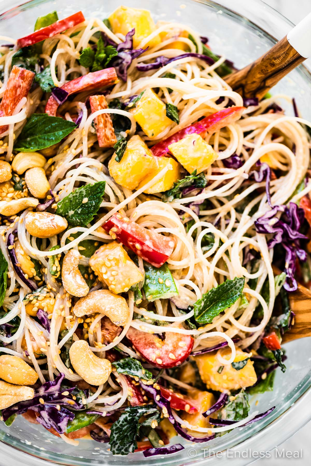 Thai noodle salad in a bowl with lots of mangos and red peppers.