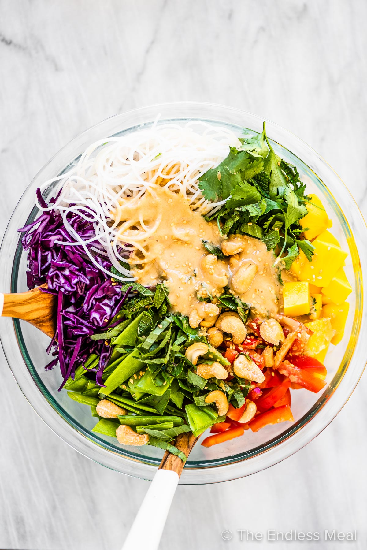All the ingredients for this Thai noodle salad in a glass bowl with wooden serving spoons.