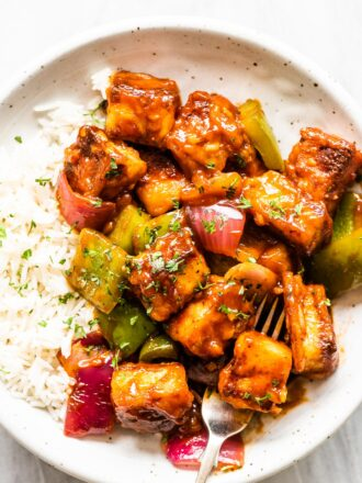 Sweet chili paneer on a white plate with rice.