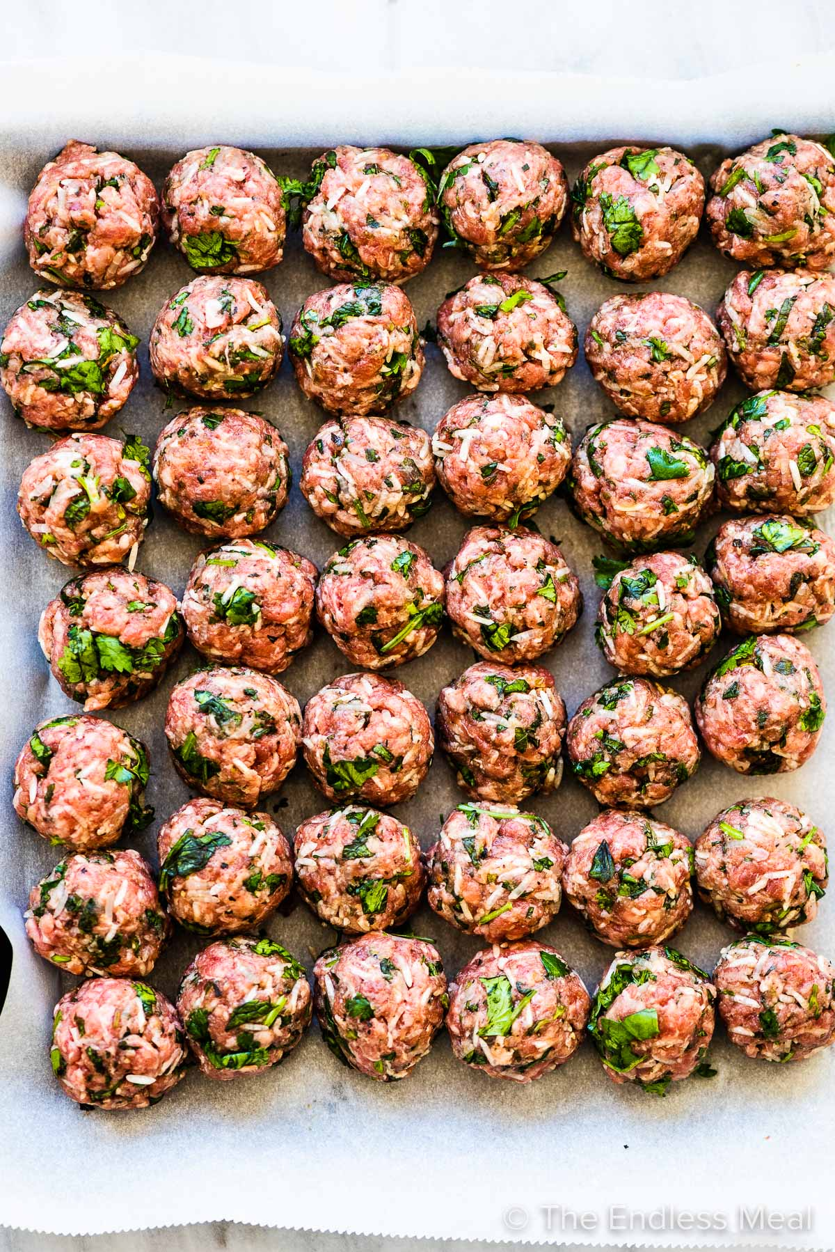 Albondigas (Mexican meatballs) lined up on a baking tray.
