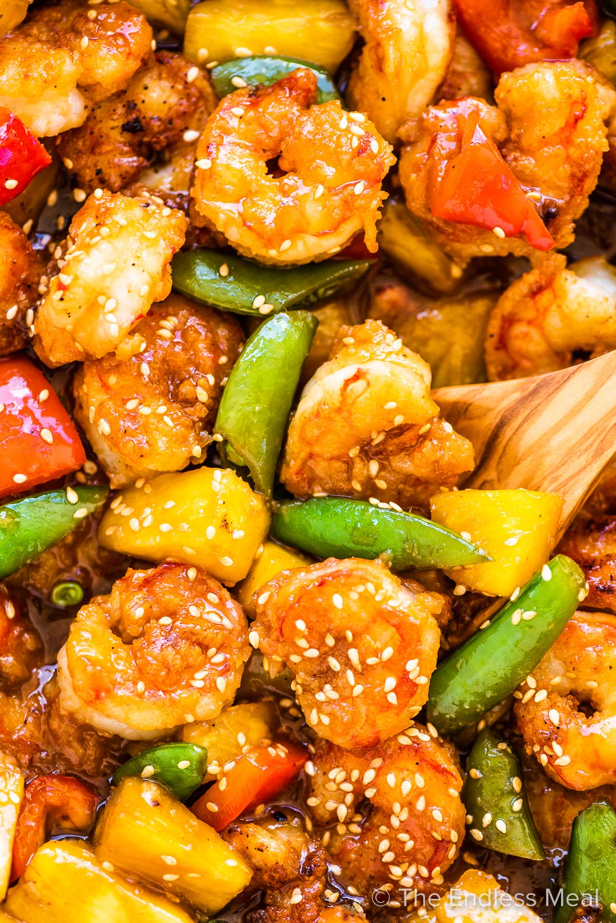 A close up of pineapple shrimp stir fry with red peppers and snap peas.