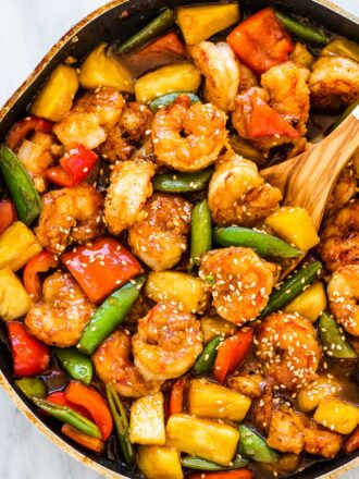 A frying and filled with pineapple shrimp stir fry and lots of veggies.