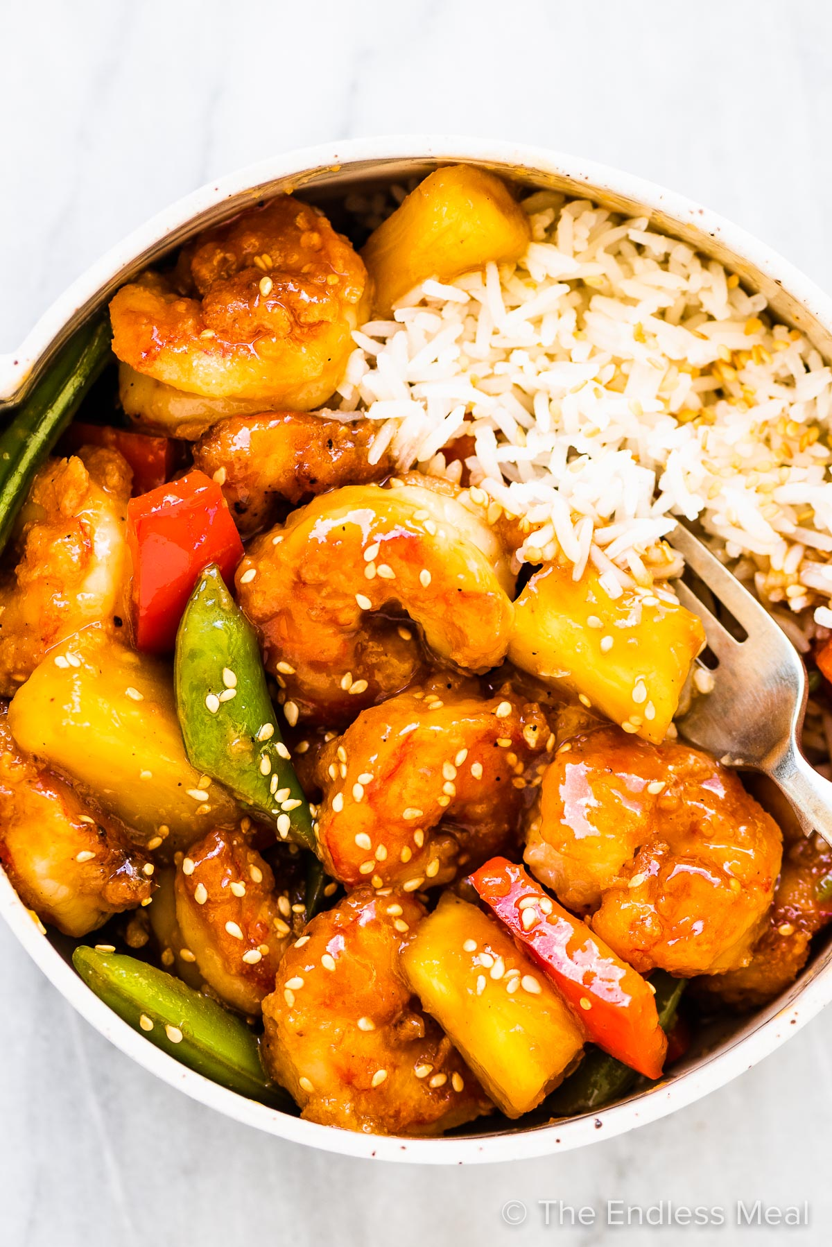A bowl with rice and stir fried shrimp and pineapples.