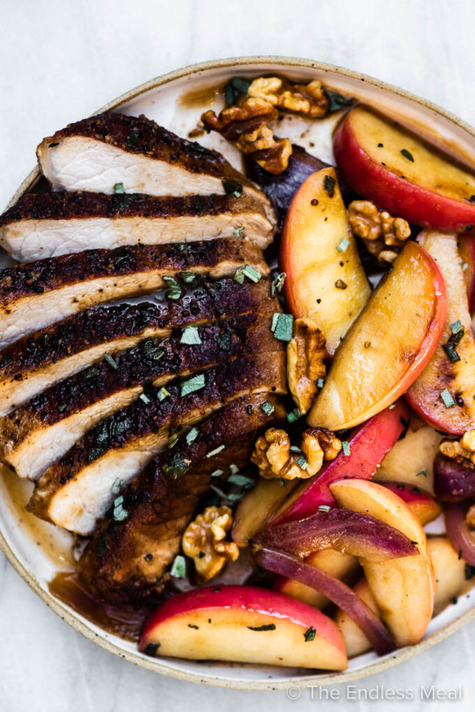 Sliced pork chops with apples and onions on a plate.