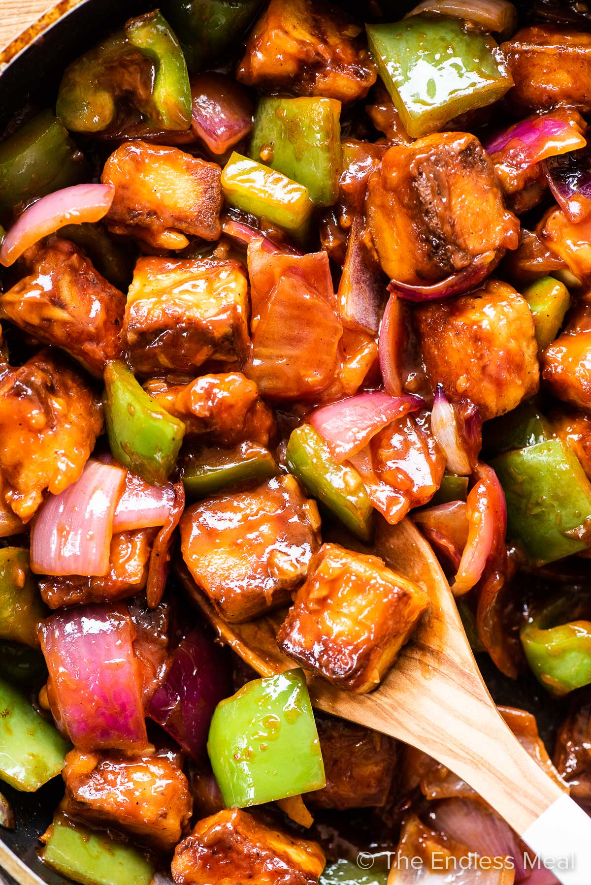 Sweet chili paneer in a pan with green onions and red peppers.