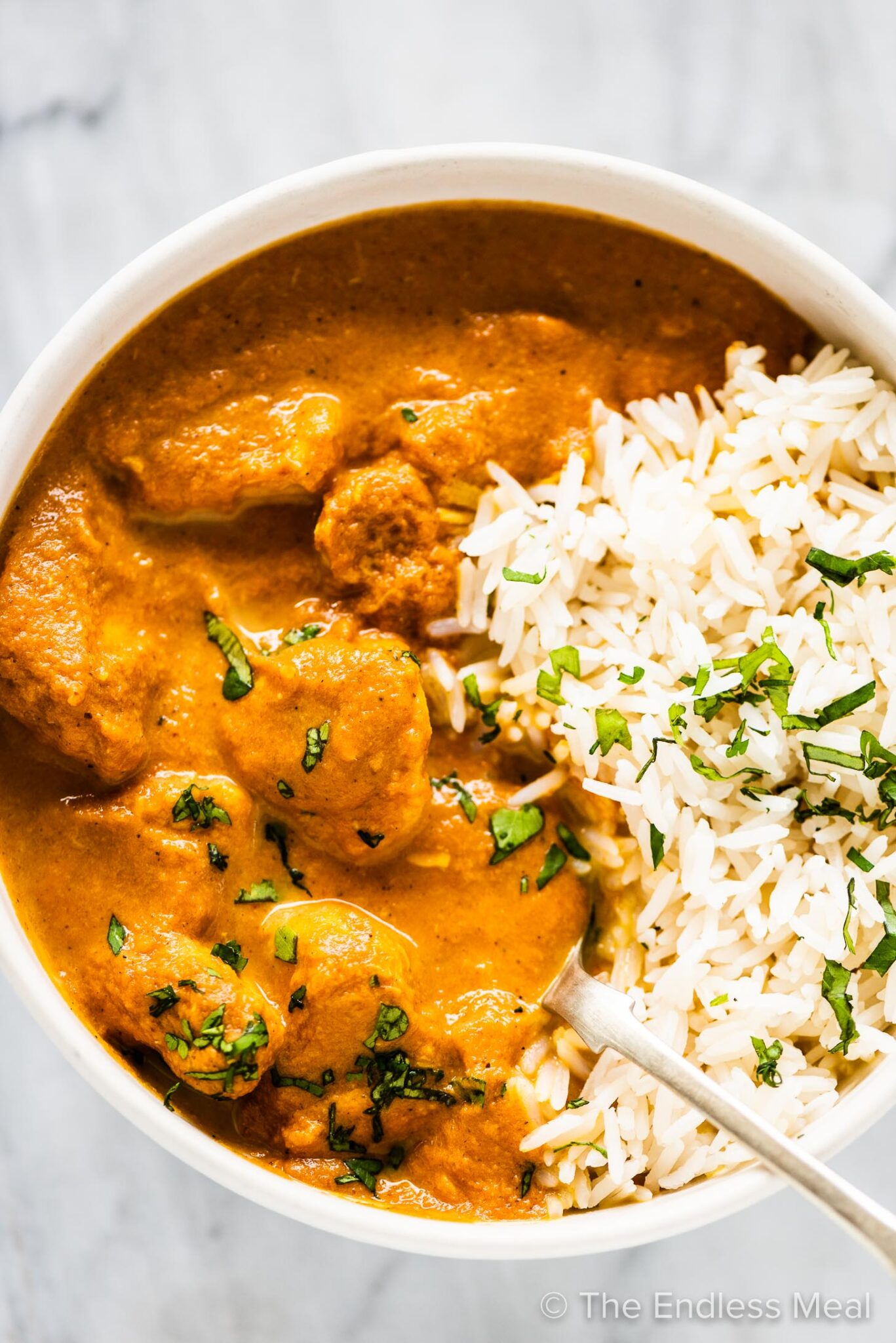 Slow cooker butter chicken in a bowl with rice.
