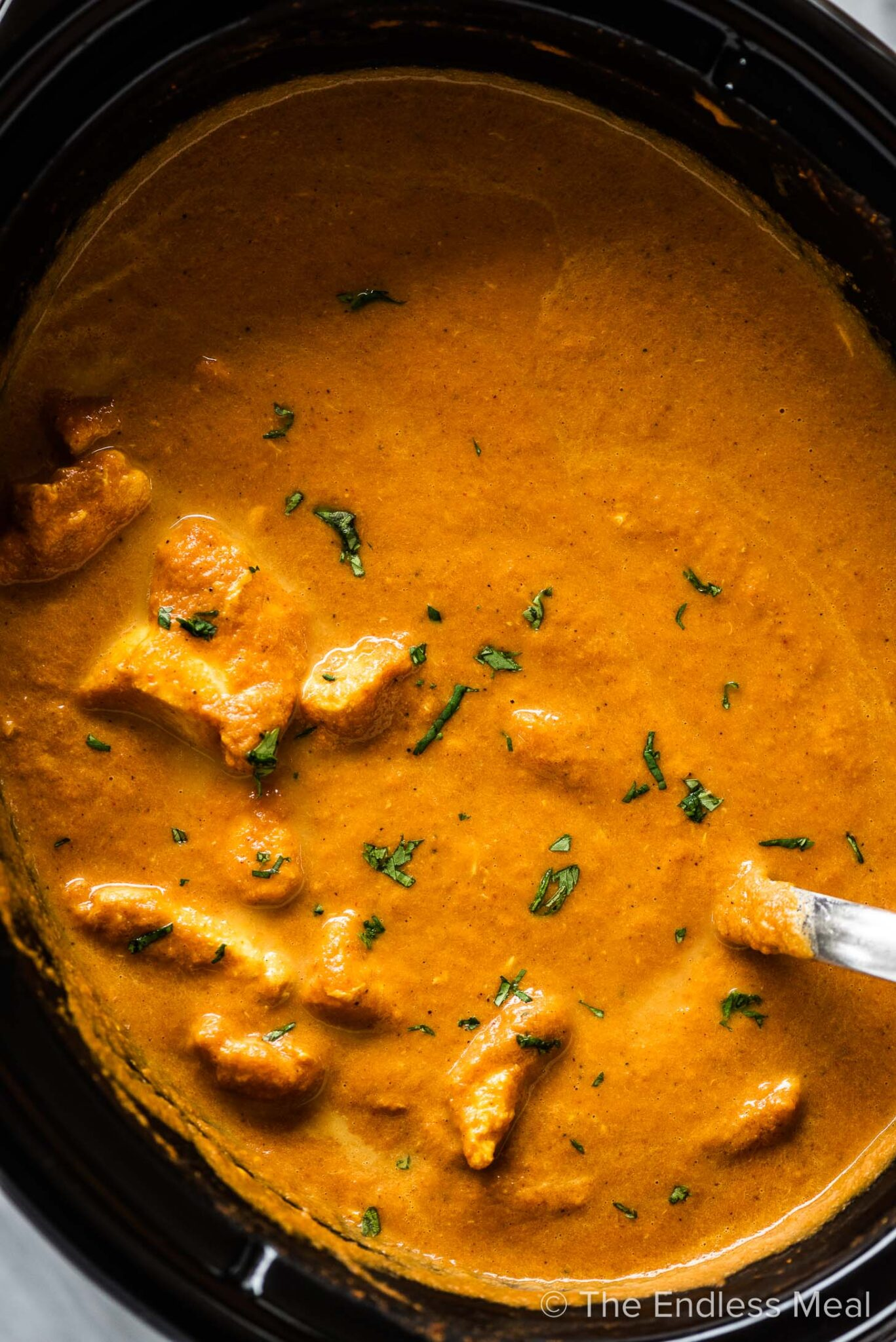 Crockpot butter chicken in a slow cooker with a ladle taking a spoonful.